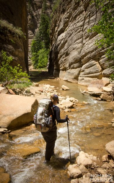 A traveler concentrates on their footing while hiking The Narrows.
