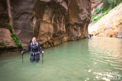 A hiker in a trip through The Narrows with water above her knees.