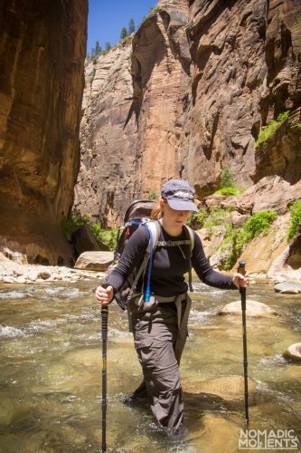 A hiker using hiking poles to steady themselves in the swift waters of the Virgin River