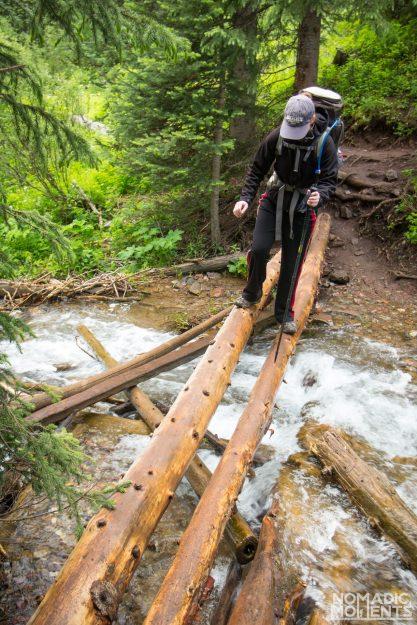 A backpacker crosses Clear Creek