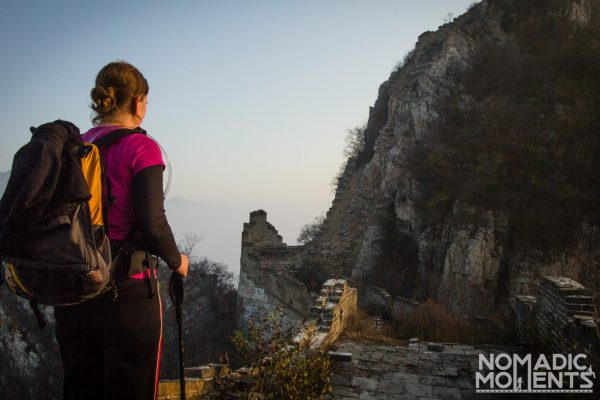 A hiker looking at a very steep section of the unrestored part of the Great Wall of China