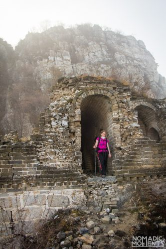 A hiker standing in the doorway of a crumbling tower