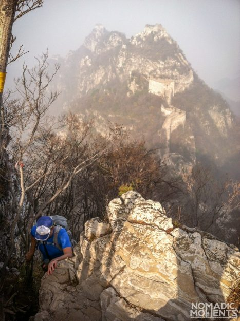 A hiker crawling up a cliff above the Jiankou sections of the Great Wall