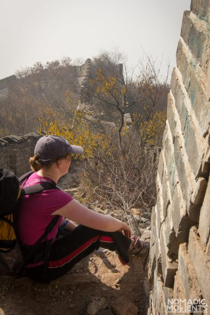 A hiker sits on the unrestored section of the Great Wall of China