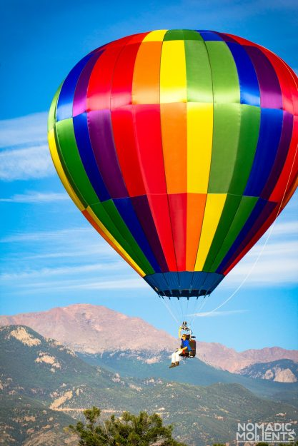 A single hot air ballon in front of Pikes Peak