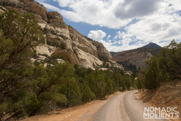 A gravel road with a canyon wall.