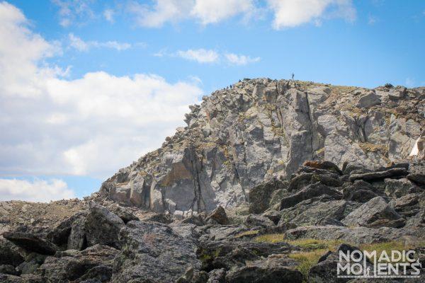 A hiker stands atop Mount Ida.