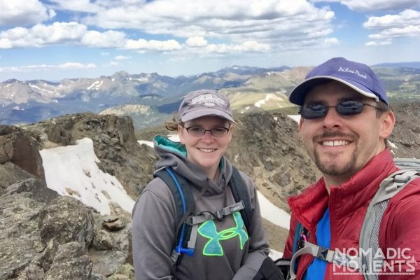 Two hikers sit on top of Mount Ida.