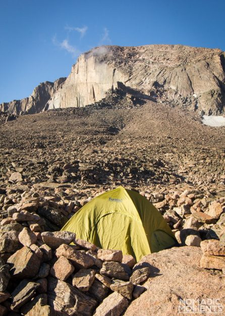 A tent set up and surrounded by a rock wall with a mountain in the background.