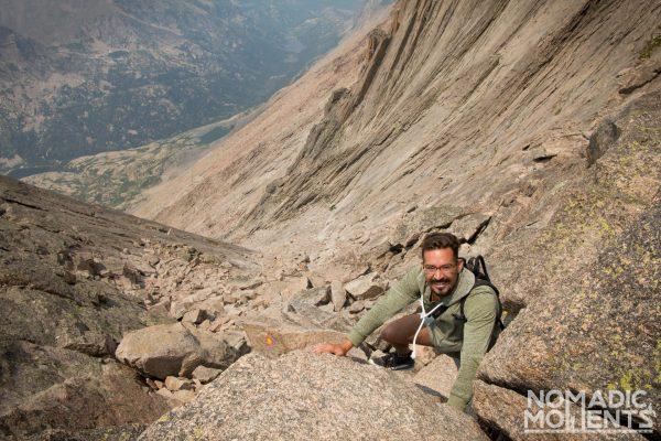 A hiker uses hands and feet as he climbs up a bouldery terrain.