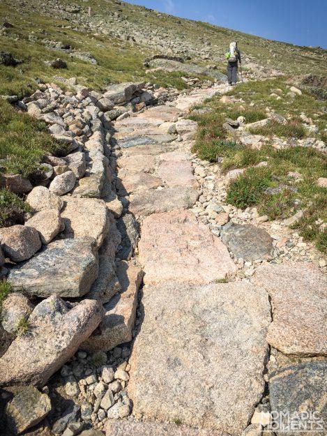 A hiker walks along a trail of flat boulders.