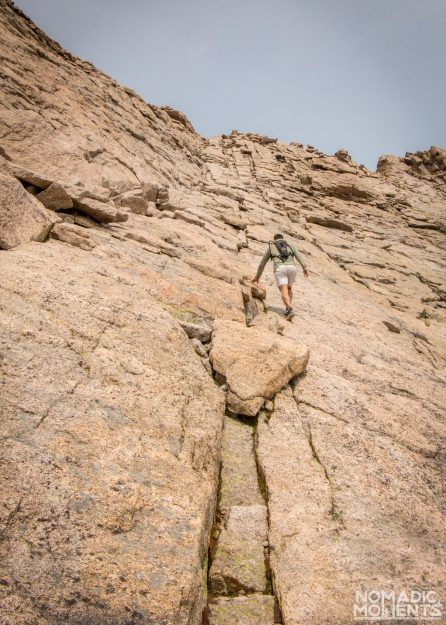 A hiker climbs up a crack on a slopped granite wall.