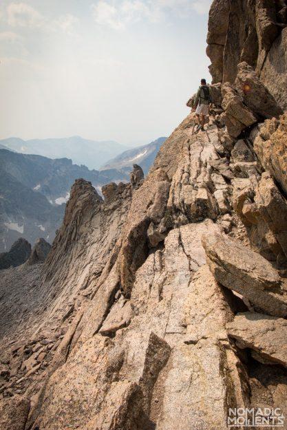 A hiker walks across a narrow rocky ledge.