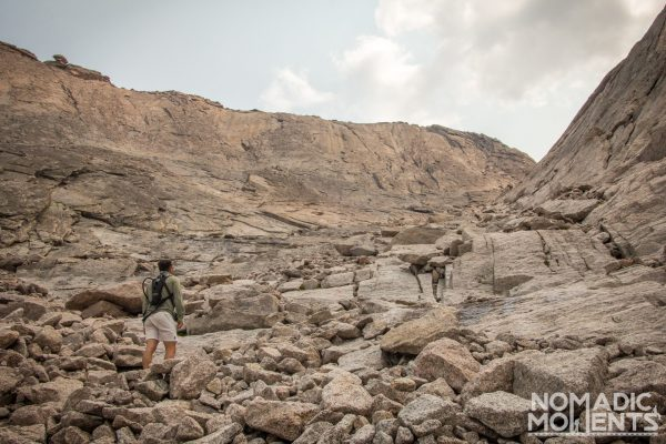 A hiker stands on rocky terrain looking up at the treacherous path ahead.