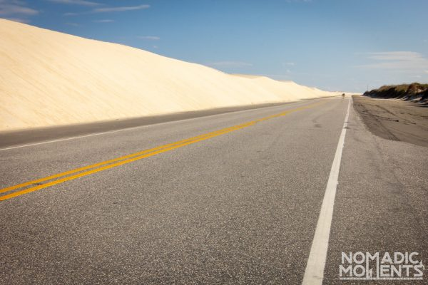 A road runs alongside a long sand dune in the Outer Banks.