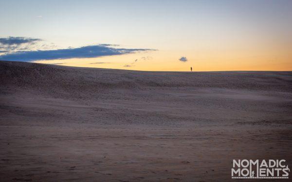 A hiker on top of a Jockey's Ridge sand dune at sunset.