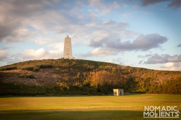 A large monument to the Wright brothers sitting on a grassy hill.