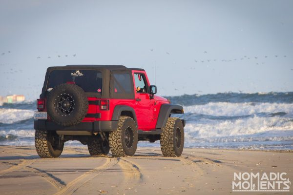 A jeep parked on an Outer Banks beach with the crashing waves in the background.