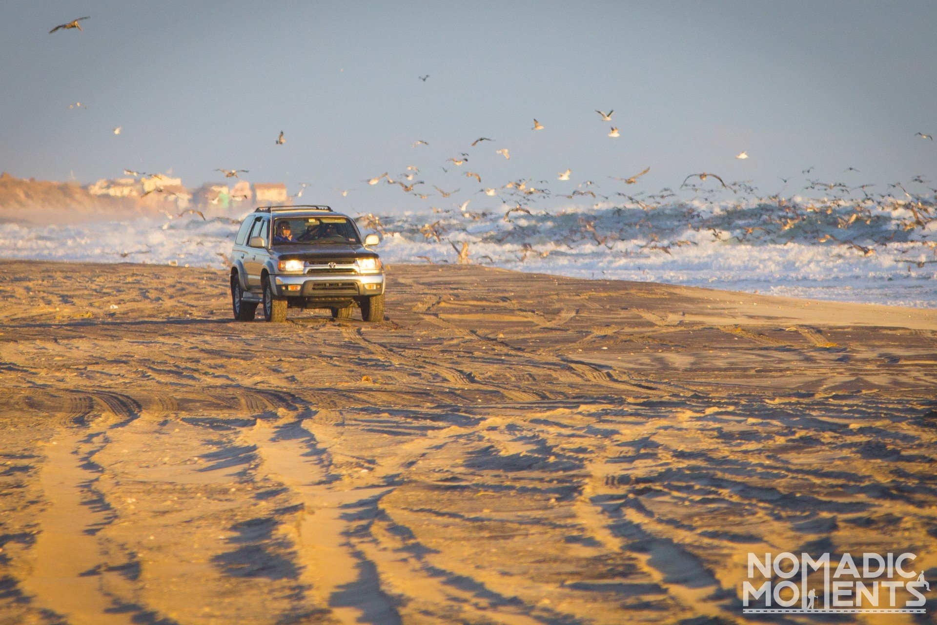 A vehicle driving on a beach while visiting the Outer Banks
