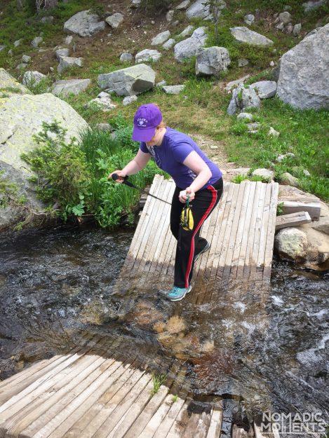 Jennifer hops over a broken bridge on the Buchanan Pass trail.