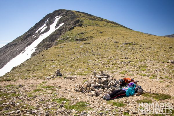 A hiker takes a nap next to a cairn.