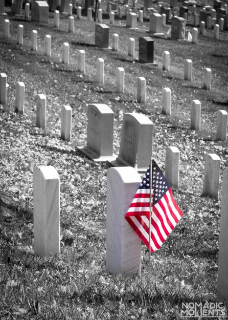 An American Flag and the tombstones of Arlington National Cemetery.