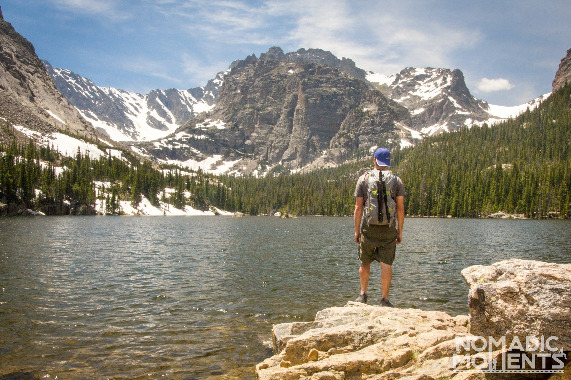 A hiker stands on the shore of The Loch after hiking on one of the best trails in Rocky Mountain National Park.